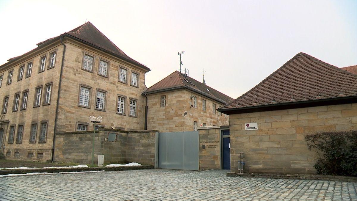 Die Zufahrt zur JVA mit einem Schiebetor, daneben alte Gebäude aus Sandstein.