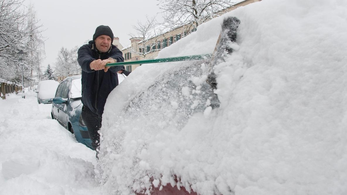 Mann fegt sein Auto von Schnee frei