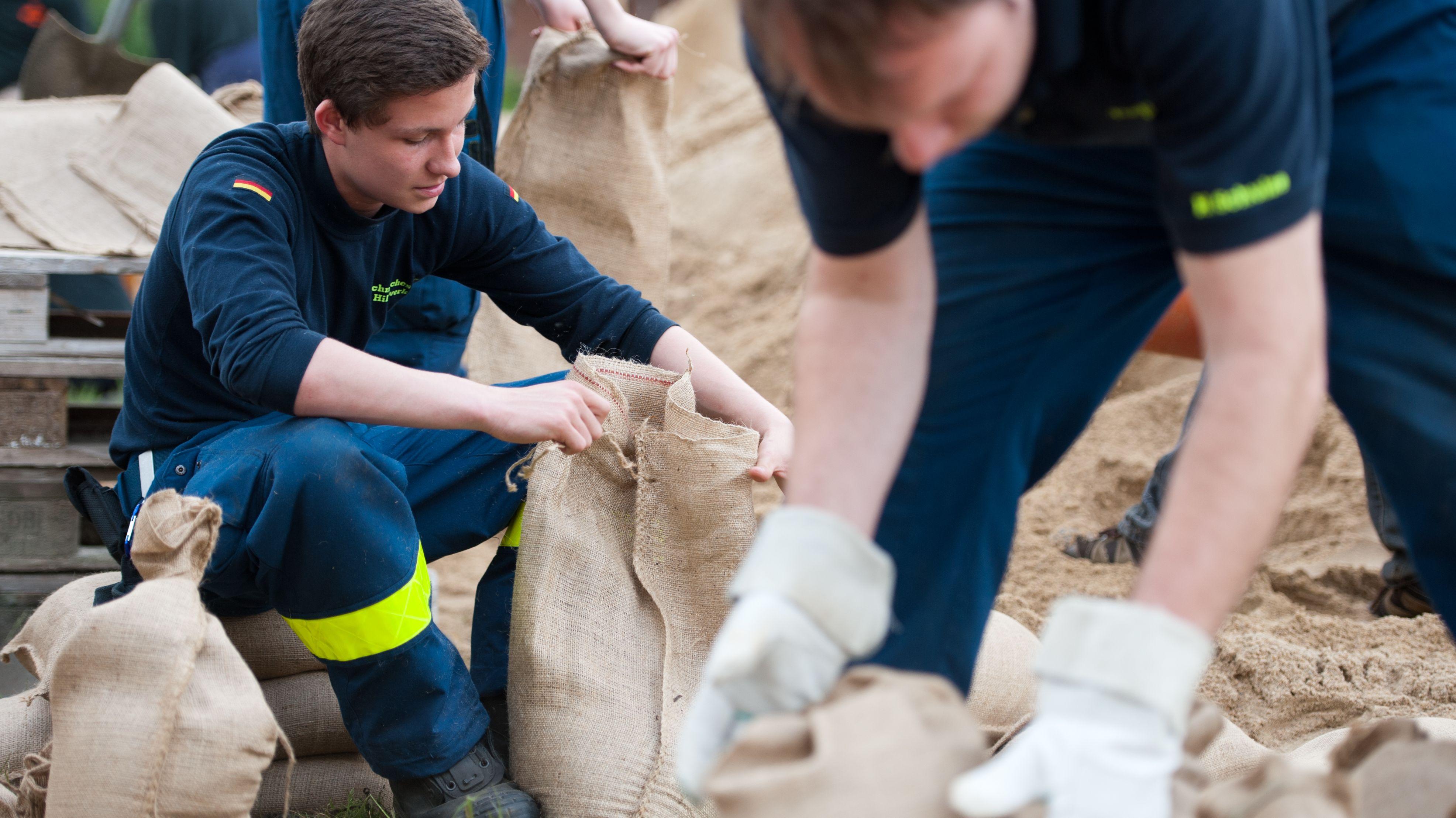 Einsatzkräfte des THW mit Sandsäcken
