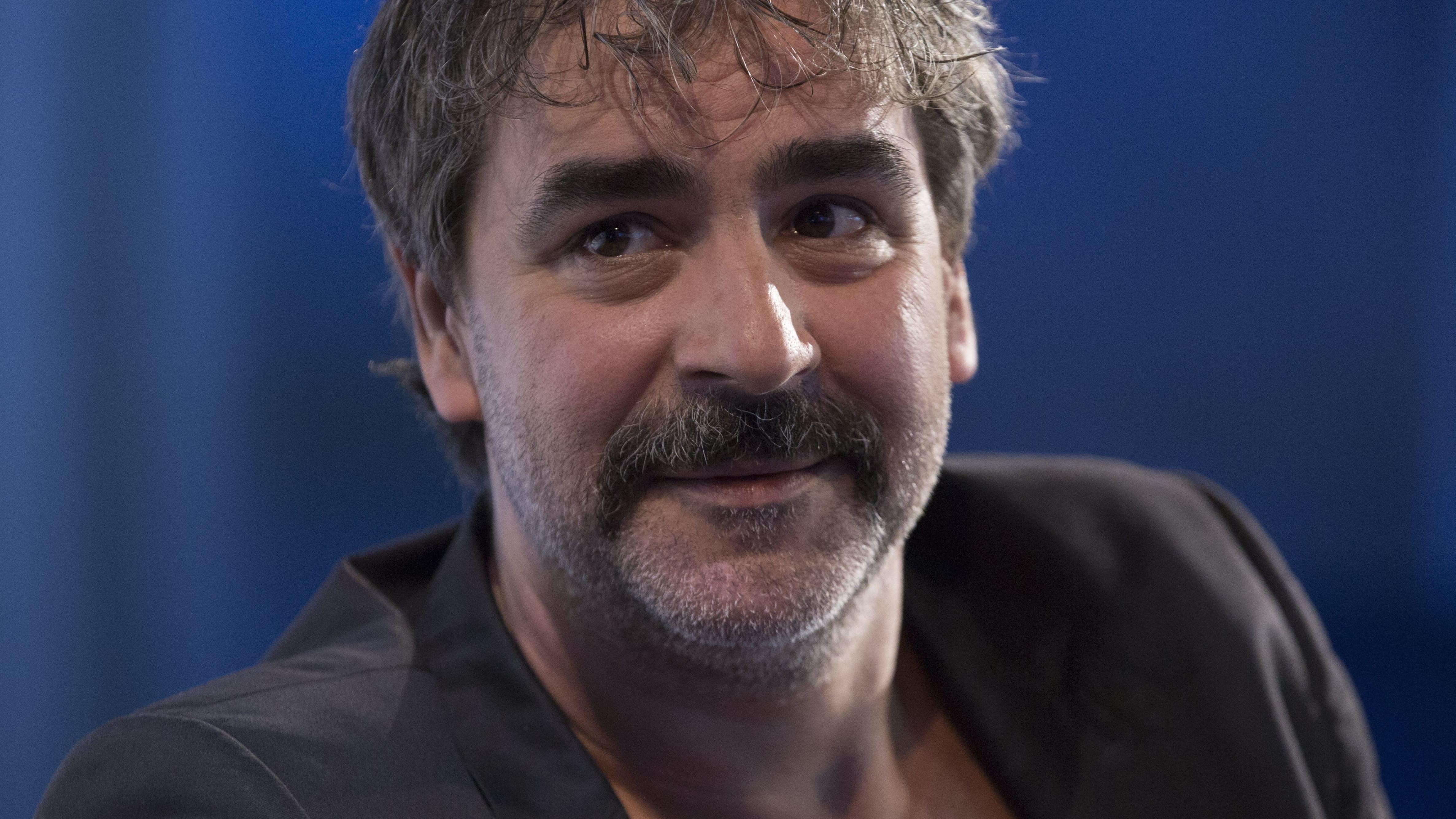 Journalist und Autor Deniz Yücel blickt vor blauem Hintergrund vorsichtig lächelnd aus dem Bild heraus