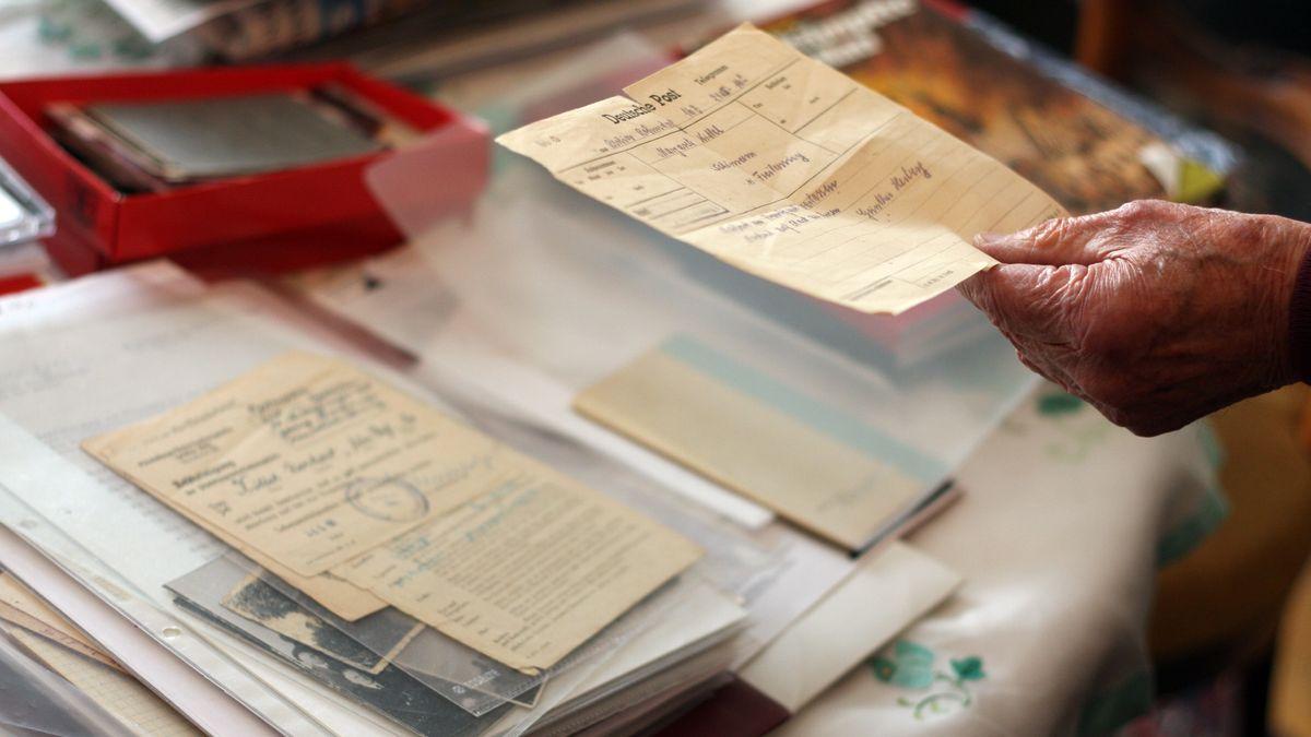 Dokumente liegen auf dem Tisch in Norbert Kittels Wohnung, darunter Fotos und Notizen.