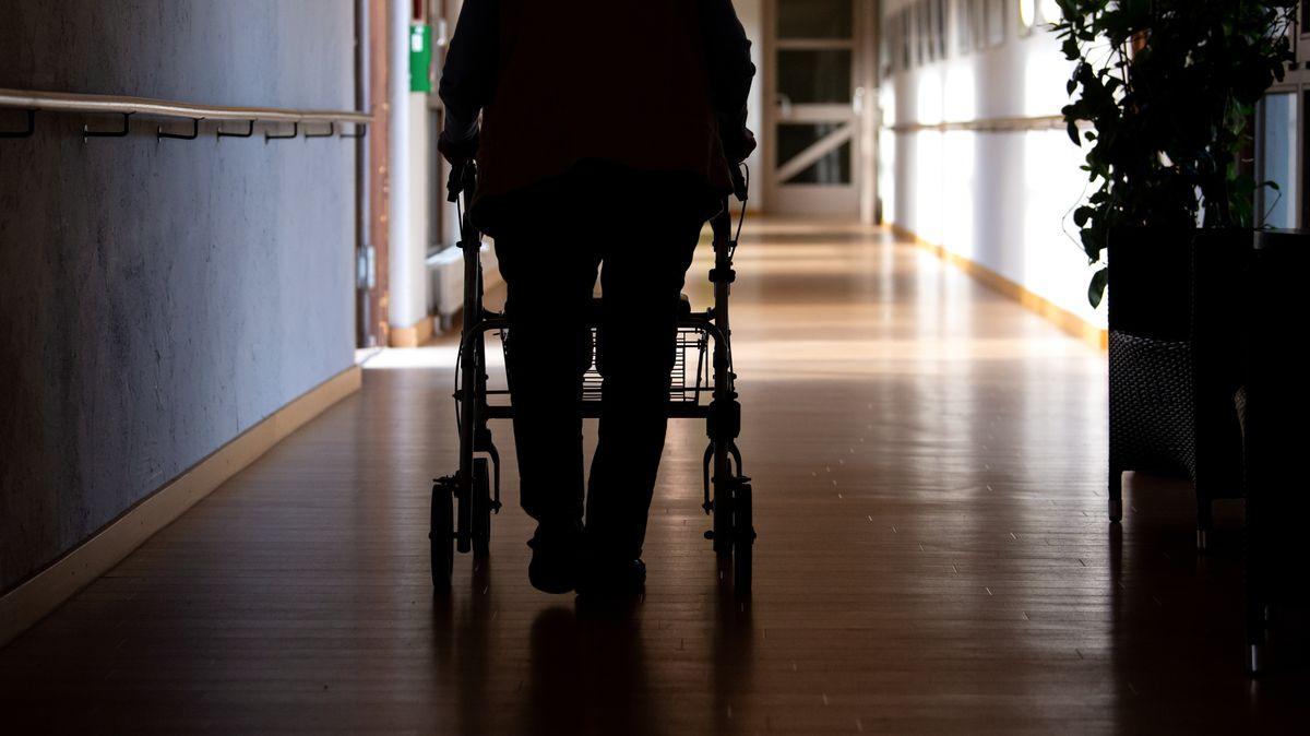 Eine Seniorin läuft mit ihrem Rollator über den Flur eines Pflegeheims