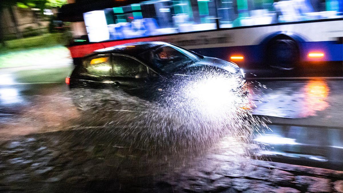 Ein Auto fährt durch eine Unterführung in Unterhaching, die nach einem Hitzegewitter mit Starkregenschauer überschwemmt ist.