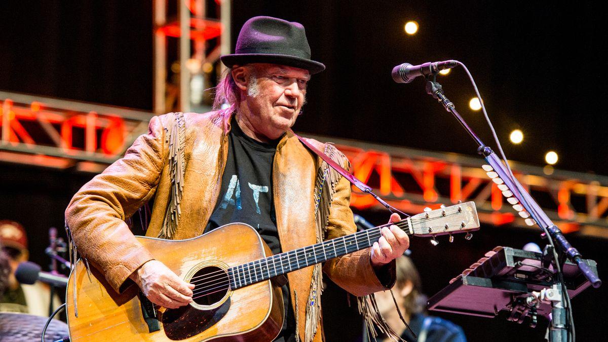 Ein Mann mir hellbrauner Lederjacke, schwarzem Hut und Gitarre