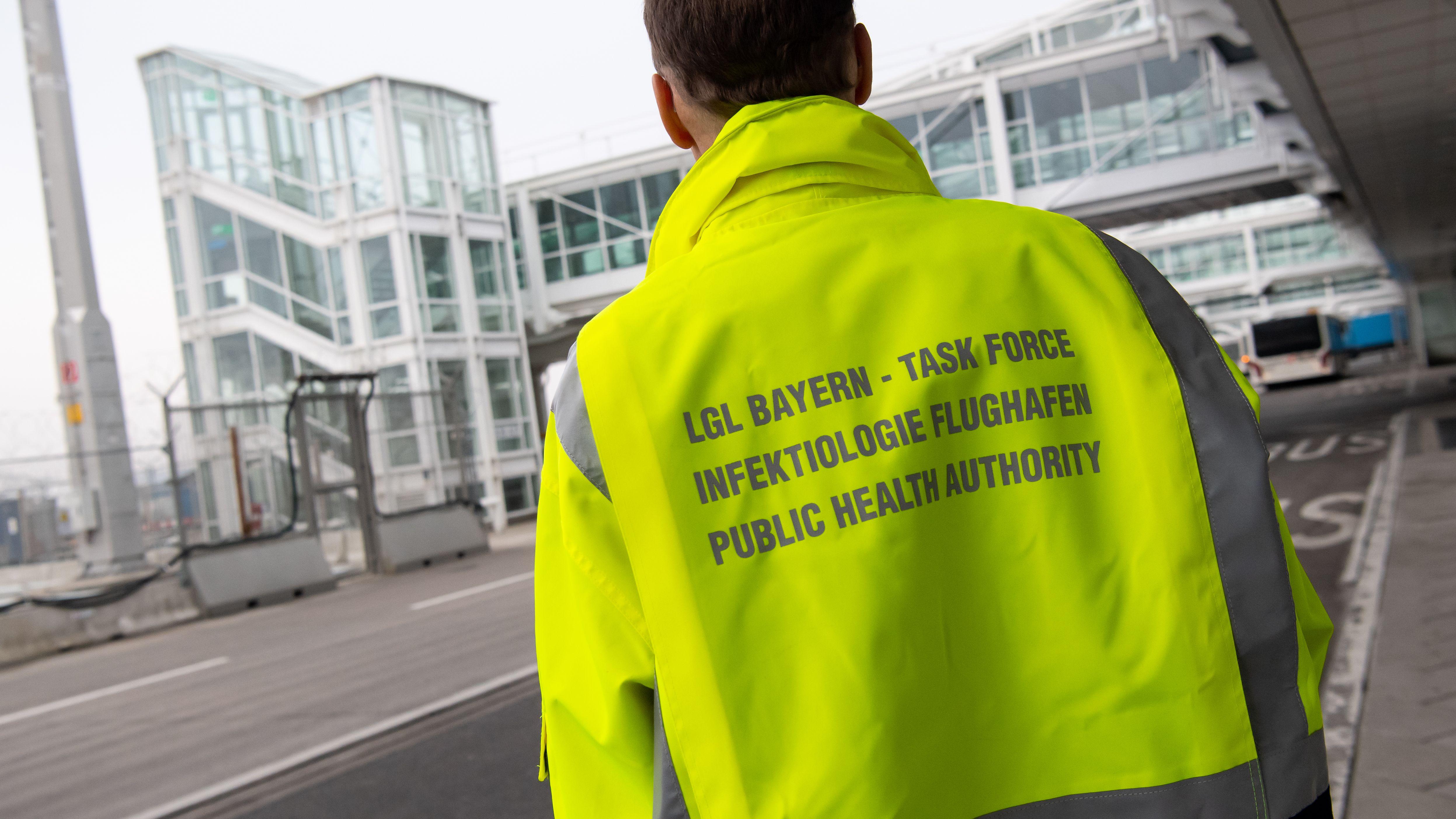 """""""Task Force - Infektiologie Flughafen"""" steht auf der Jacke eines Mitarbeiters der """"Task-Force Infektiologie"""" am Flughafen München."""