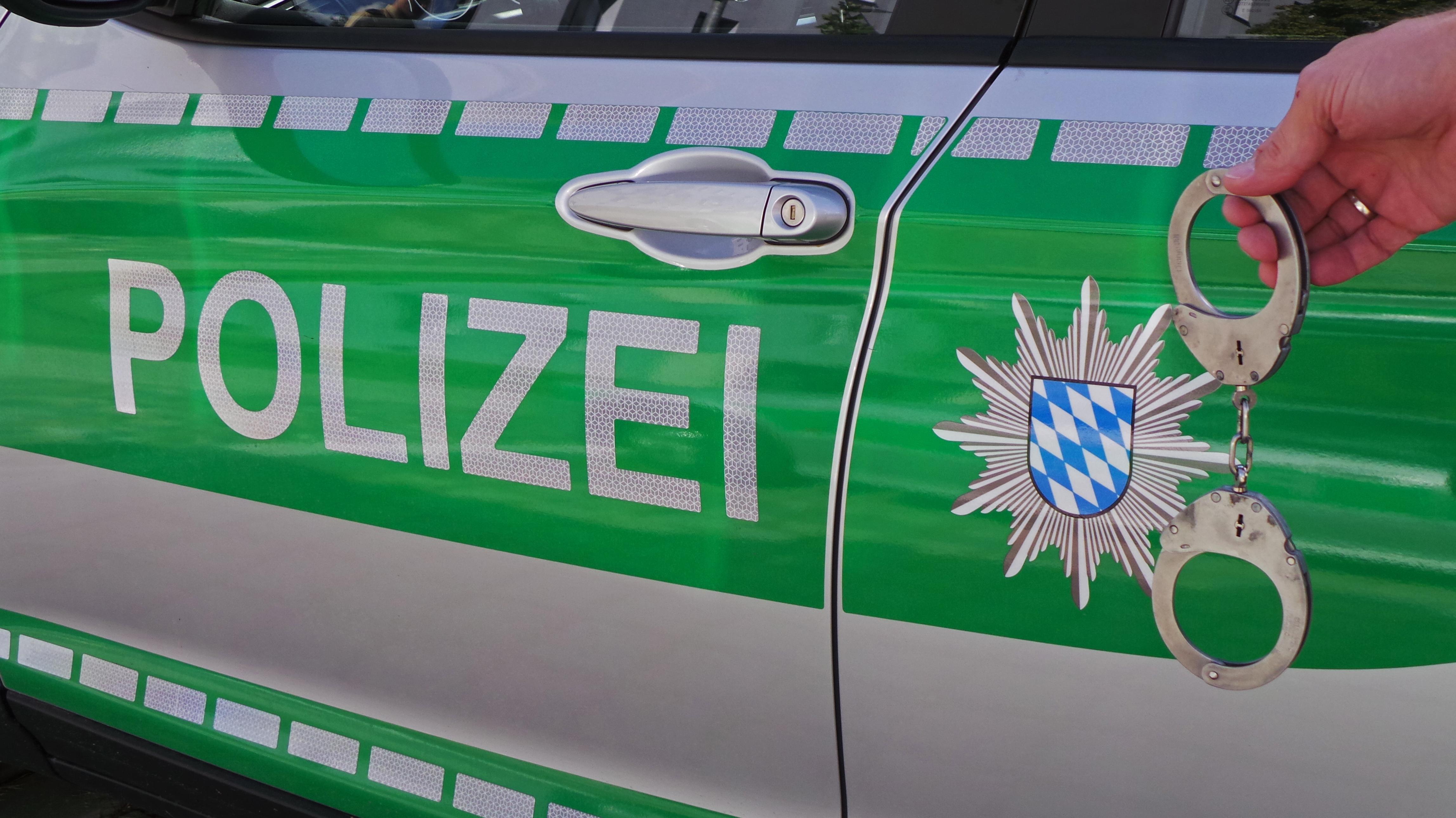 Polizeiauto seitlich mit bayerischem Wappen und Schriftzug Polizei und Handschellen, Polizei, Unfall, Verbrechen, Kriminalität.