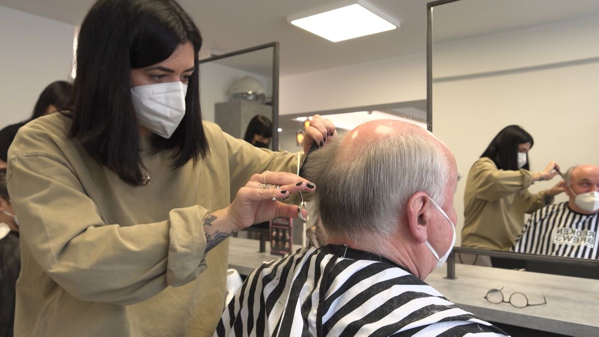 Eine Friseurin schneidet einem grauhaarigen Mann die Haar