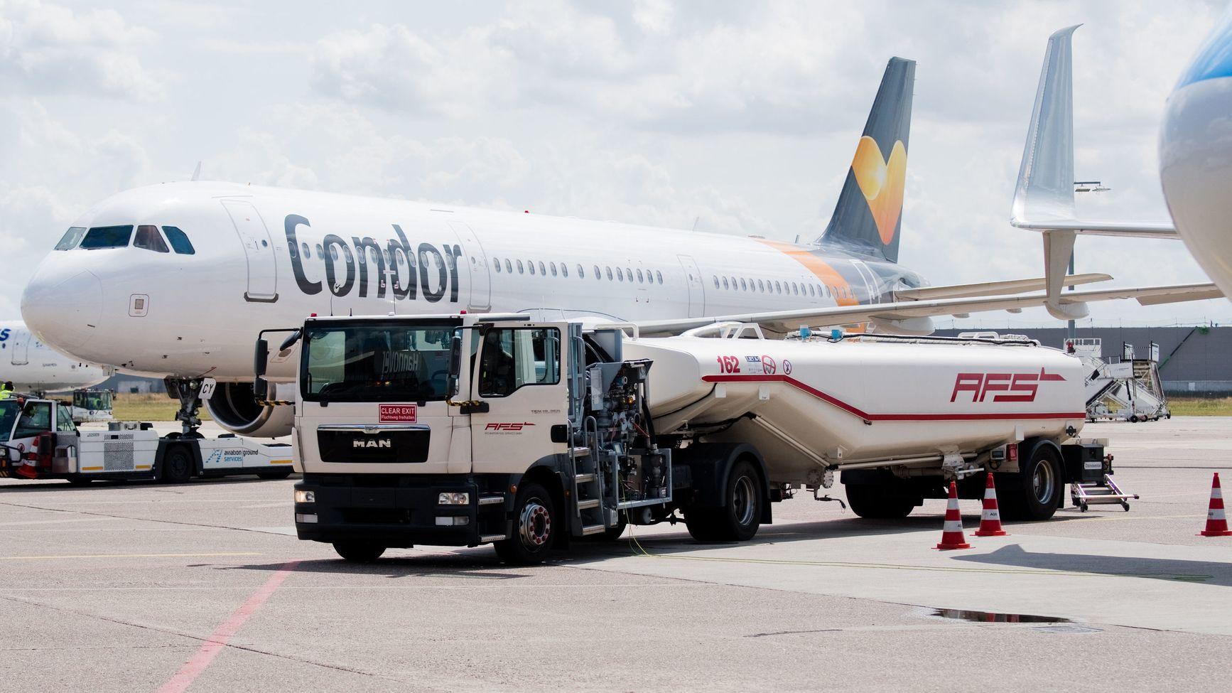 Ein Tankfahrzeug steht auf einem Flughafen in der Nähe eines Flugzeugs.