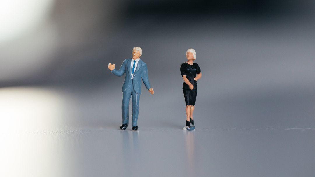Zwei Figuren im konservativen, genderpointierten Dresscode: Sie im engen Kostüm, er im Anzug.