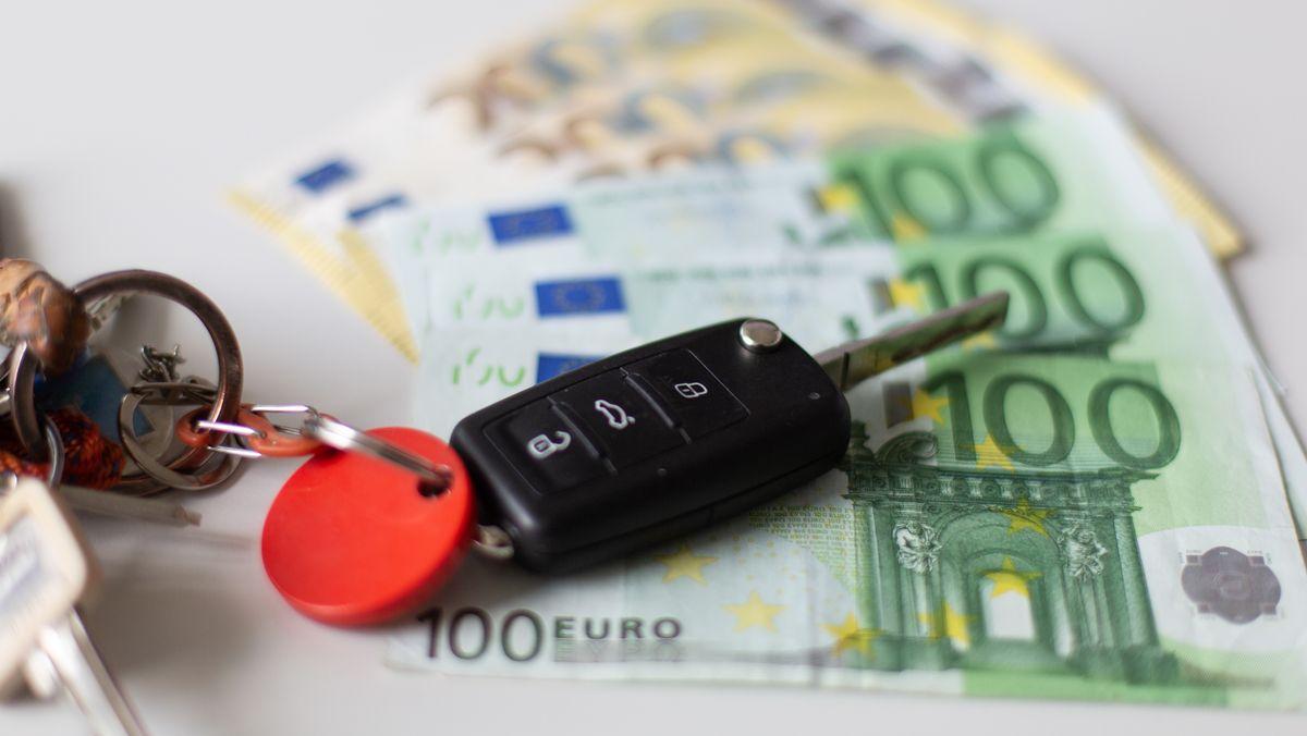 Ein Autoschlüssel, der auf 100- und 50-Euro-Scheinen liegt.
