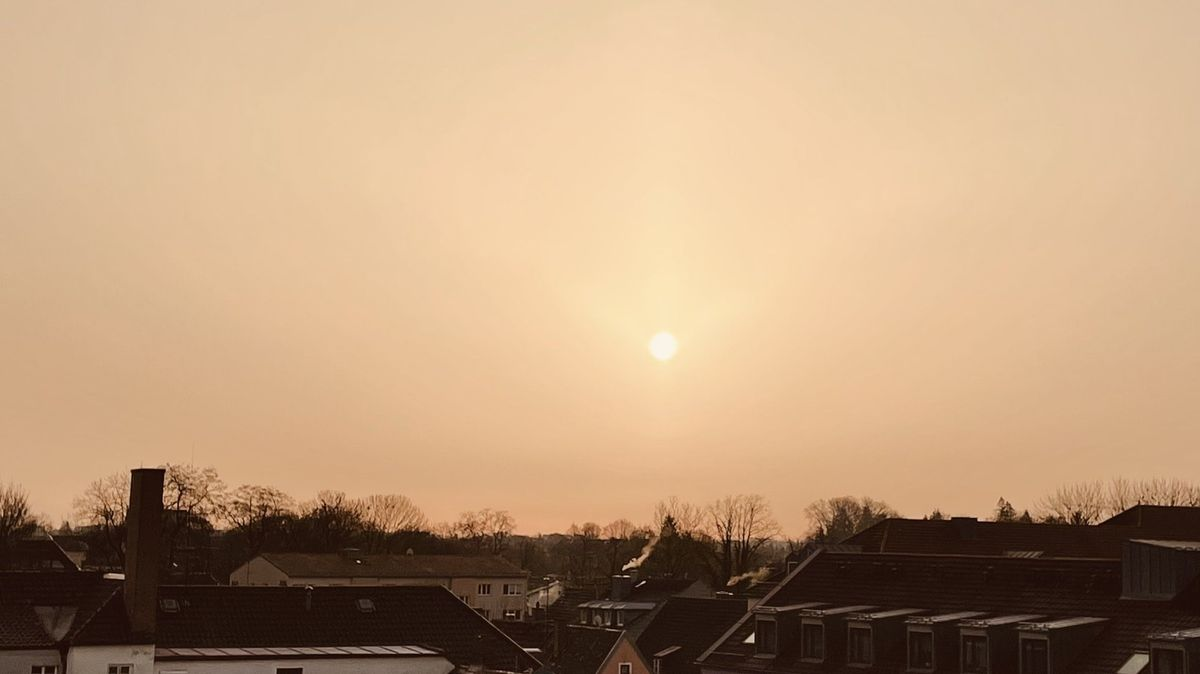 Saharasand liegt in der Luft und dimmt die Sonne, als sie am 23. Februar über Erding aufgeht