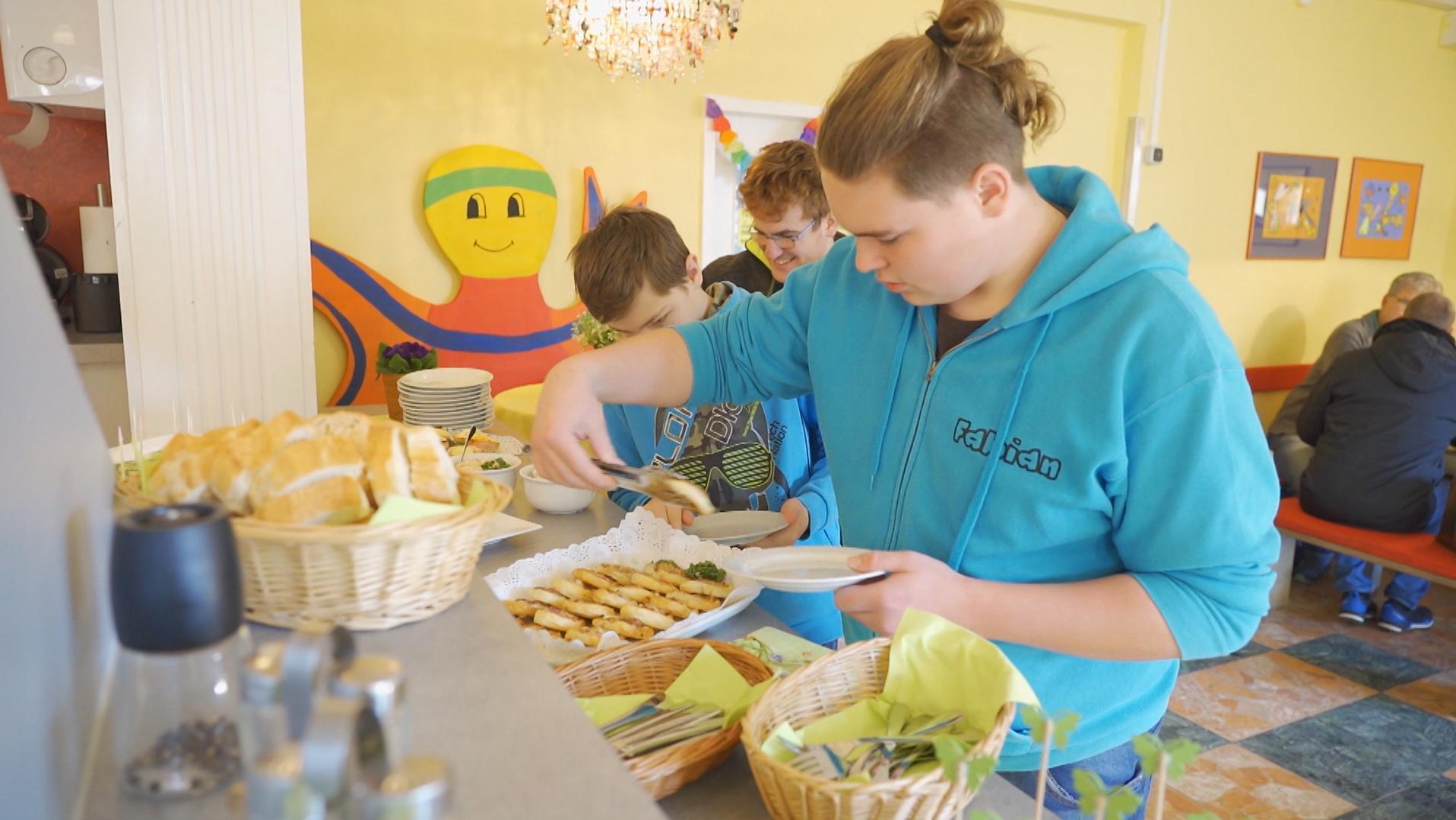 Schüler holen sich an einer Theke eine Frühstück