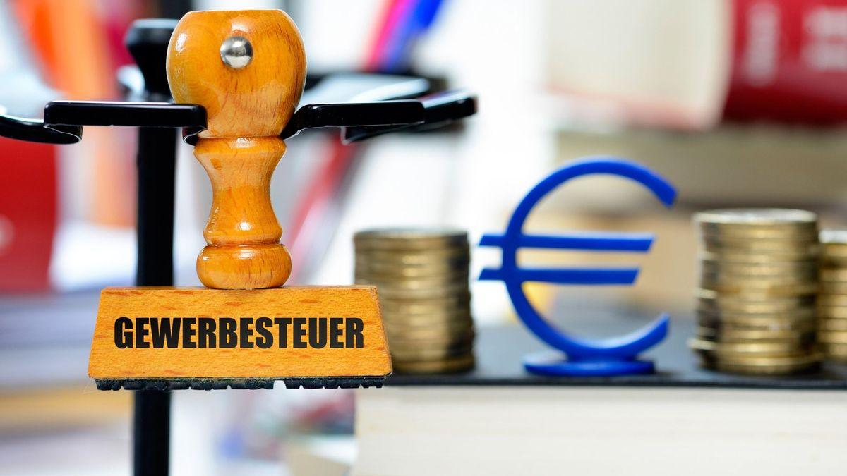 """Ein Stempel aus Holz mit der Aufschrift """"Gewerbesteuer"""" hängt an einem Stempelkarussell, dahinter aufgestapelte Münzen mit einem symbolisierten Euro-Zeichen in Blau."""