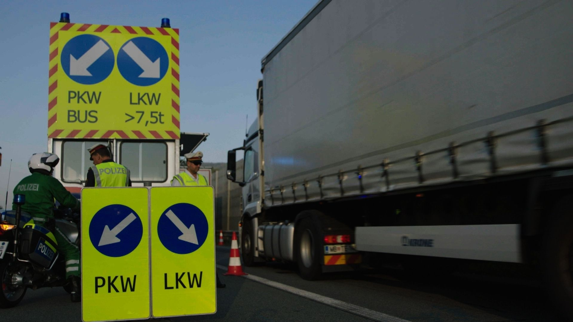 Polizisten neben Lkw bei Blockabfertigung an der Grenze bei Kufstein