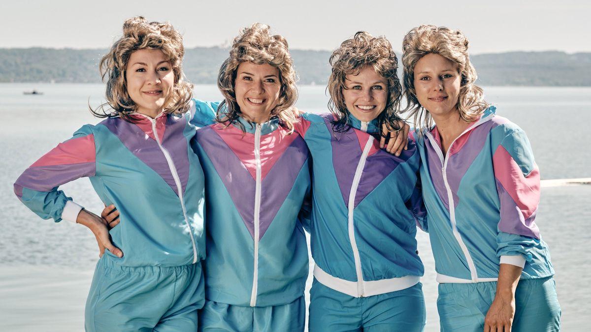 Vier Frauen stehen Arm in Arm vor einem See. Sie tragen aus der Mode gekommene Trainingsanzüge und Vokuhila-Perücken.