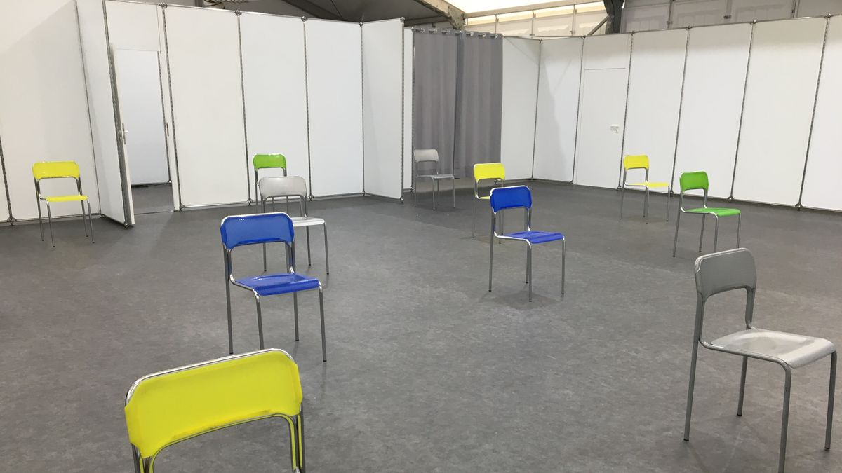 Einzelne Stühle stehen mit Abstand in einem abgetrennten Bereich im Würzburger Impfzentrum.
