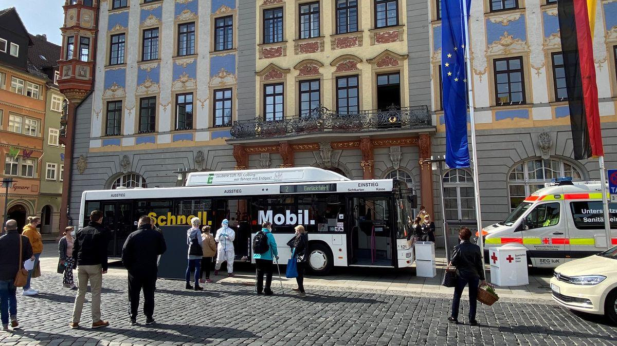 Der Testbus steht vor dem Coburger Rathaus, davor hat sich eine Menschenschlange gebildet.