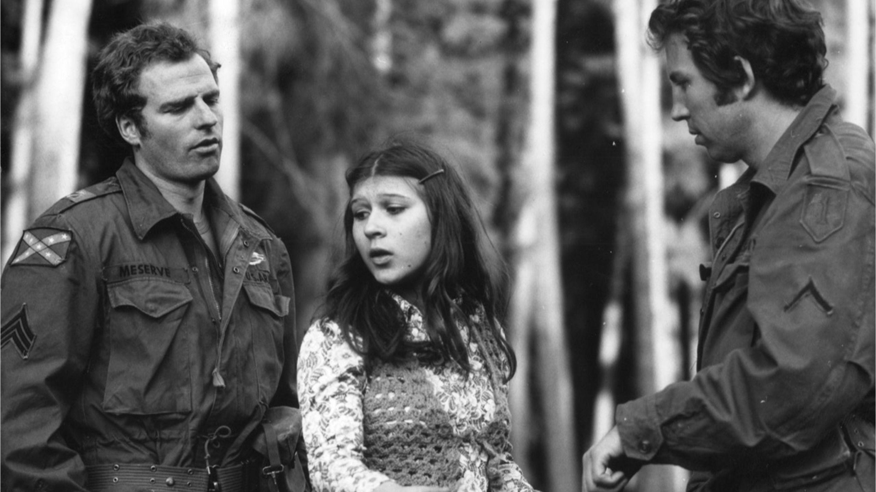 """Szene aus dem Film """"o.k."""": Eine junge Frau steht zwischen zwei Männern in Uniform."""