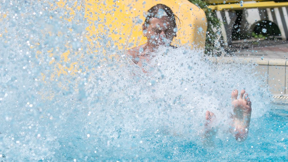 Ein Mann rutscht im Freibad ins Wasser.