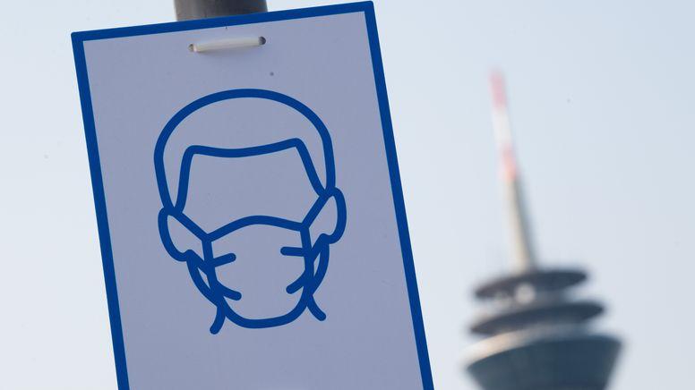 Ein Piktogramm weist auf das Einhalten der Maskenpflicht hin. | Bild:picture alliance/dpa | Federico Gambarini