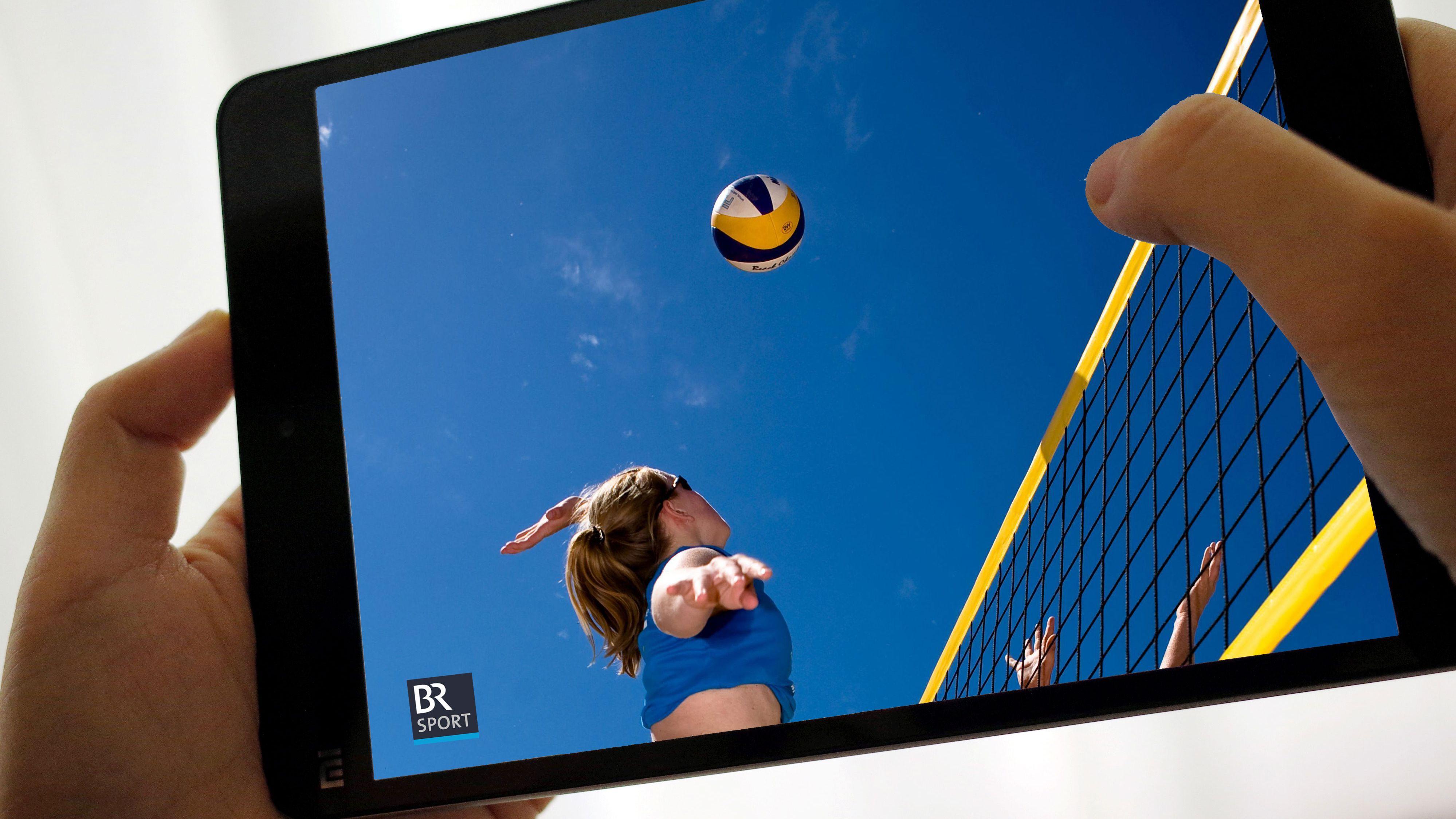 Hände halten ein Tablet, auf dem ein Beachvolleyballspiel zu sehen ist