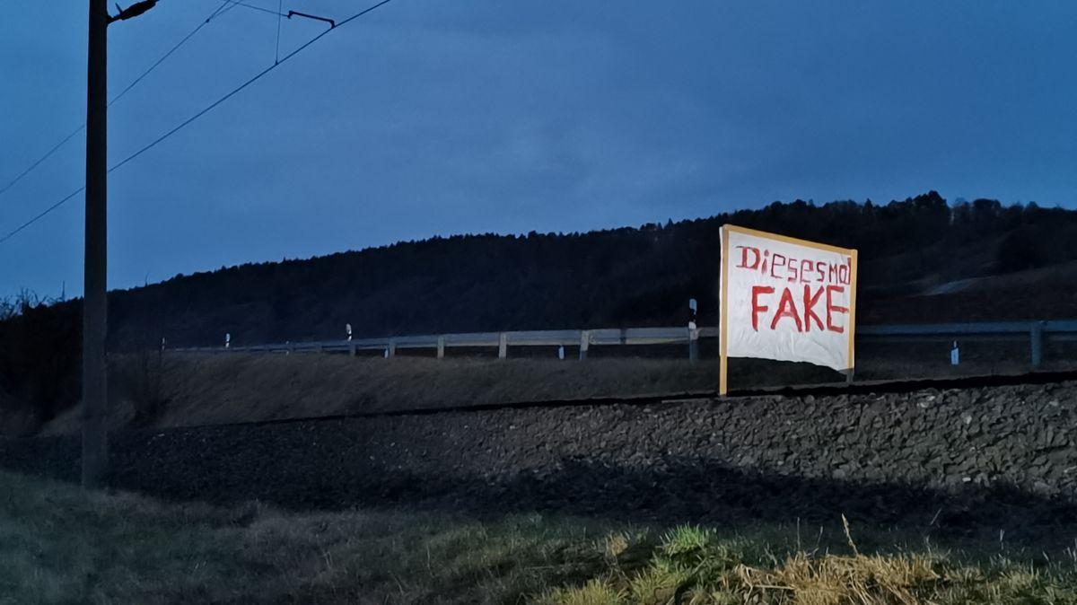 """Über Bahnstrecke gespanntes Plakat mit der Aufschrift """"Dieses Mal Fake""""."""