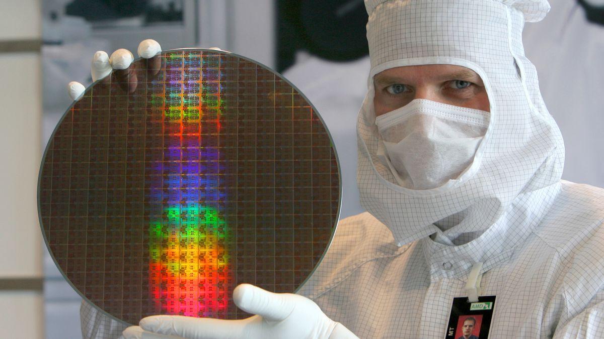 Ein Mitarbeiter in einer Fabrik hält eine Scheibe mit Mikrochips hoch.