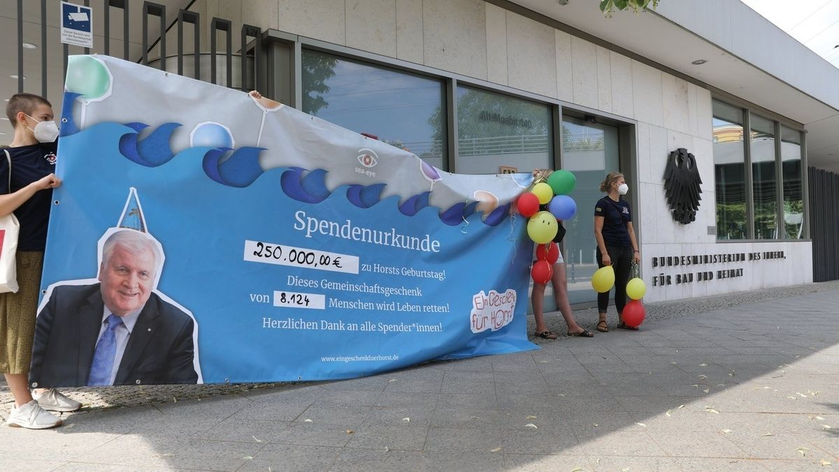 Mitglieder von Sea-Eye, die ein großes Banner mit der Spendenurkunde überreichen wollen.