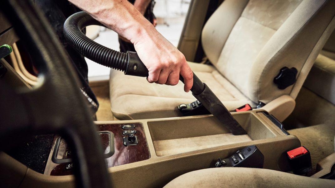 Autositze und Boden werden gesaugt.
