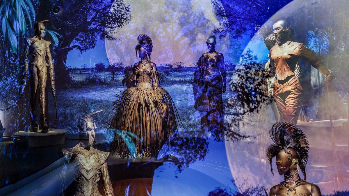 Ausstellungsansicht im Musée des beaux-arts de Montréal. Im Hintergrund eine Landschaft mit schwarzen Silhouetten von Bäumen auf leuchtendem Blau, der z.T. die Figuren überlagert. Dei Figuren wirken wie Wesen aus einem Fantasyfilm. Ihr Outfit der Figuren erinnert an Ritterrüstungen. ie