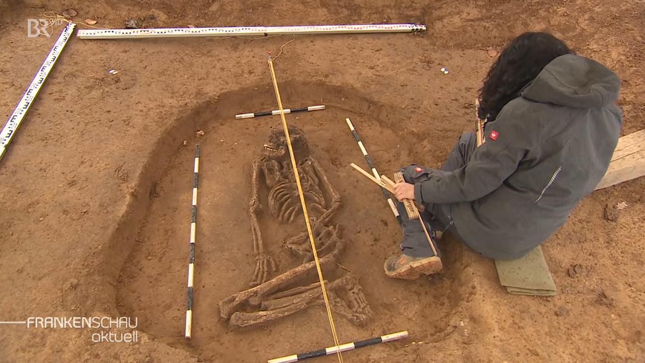 Archäologin kniet neben dem in Repperndorf gefundenen Skelett