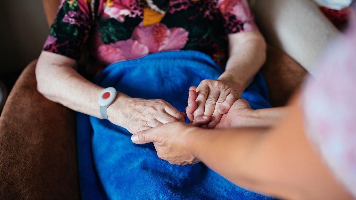 Eine ältere Frau hält die Hände einer jüngeren Frau.