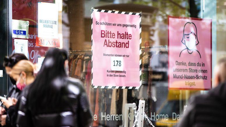 """Schilder wie """"Bitte halte Abstand"""" und """"Danke, dass du in unserem Store einen Mund-Nasen-Schutz trägst"""" vor einem Geschäft   Bild:pa/dpa/Christoph Schmidt"""
