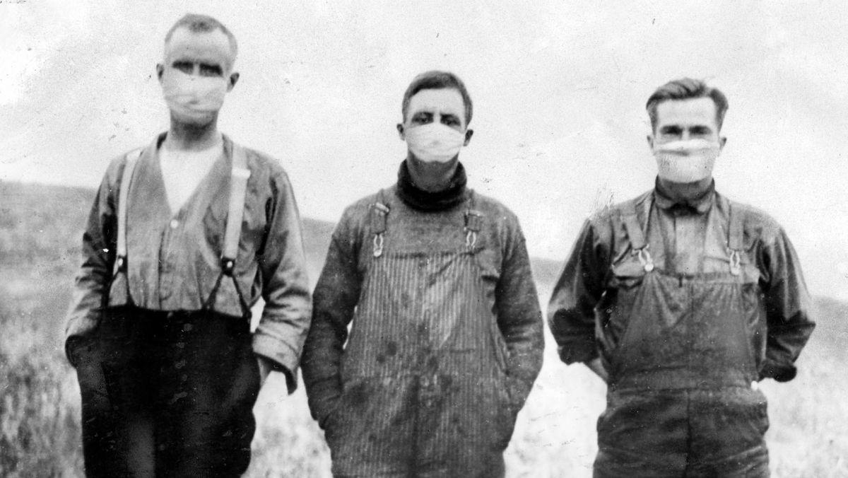 Bauern stehen auf dem Feld mit weißen Masken über Mund und Nase.