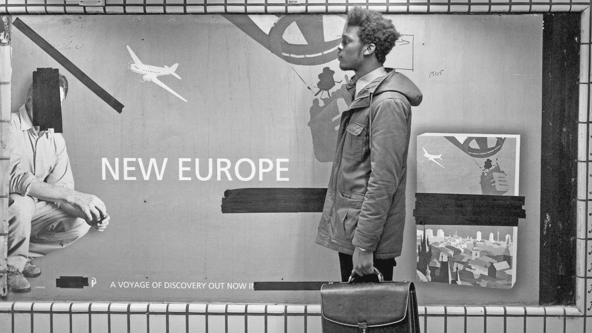 """Ein schwarzer Mann steht vor einem Plakat, """"New Europe"""""""