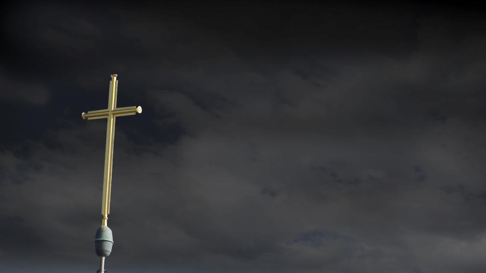 Kreuz vor dunklem Wolkenhimmel   Bild:dpa/Martin Moxter