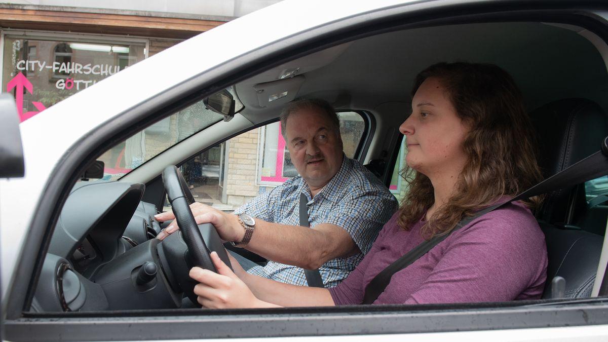 Ein Fahrlehrer erklärt einer Fahrschülerin etwas im Auto