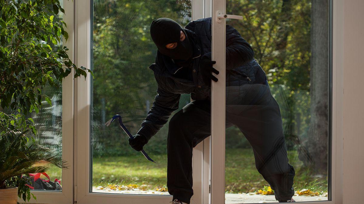 Ein Einbrecher dringt durch die Terassentür in ein Haus ein (Symbolbild)