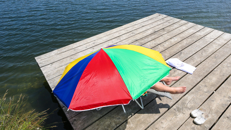 Eine Frau liegt an einem Badesee im Liegestuhl auf einer Badeinsel unter einem Sonnenschirm.