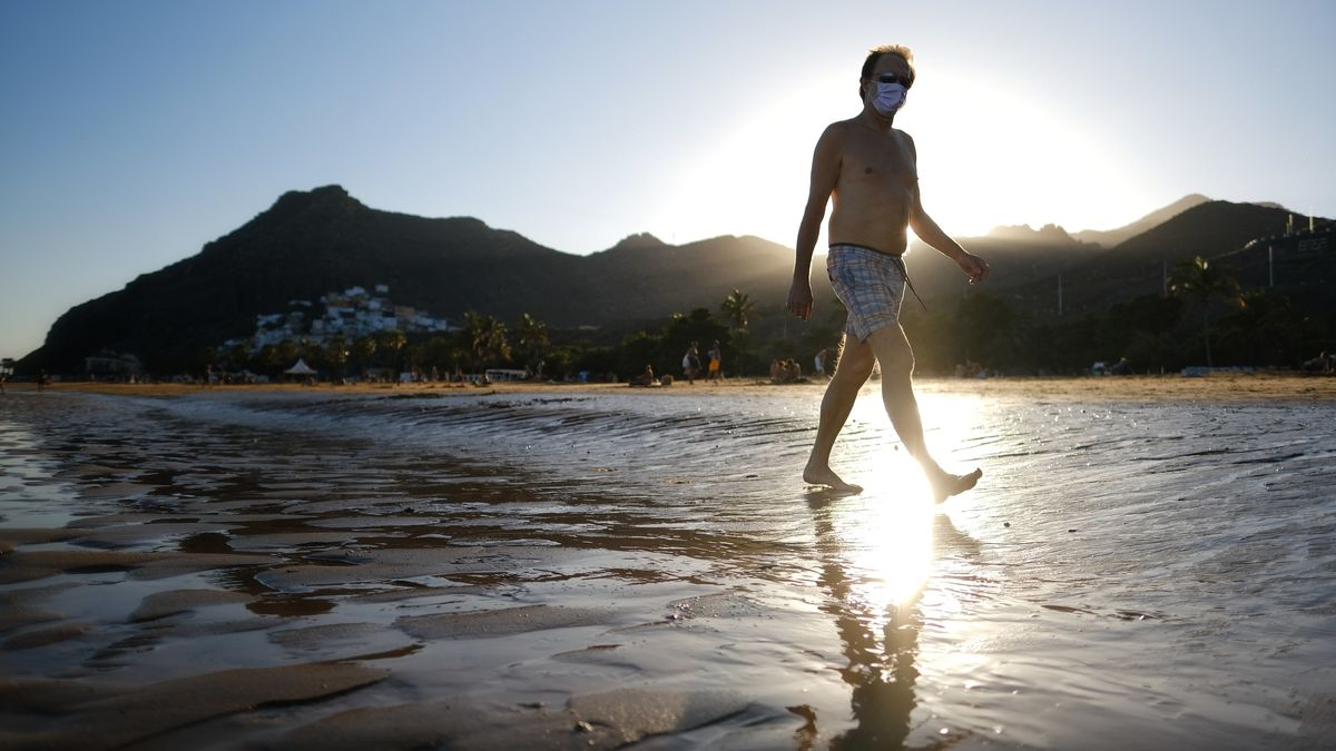 Ein Mann mit Mundschutz geht am Strand, als die Bundesregierung die Kanaren wegen steigender Infektionszahlen als Risikogebiet einstuft.