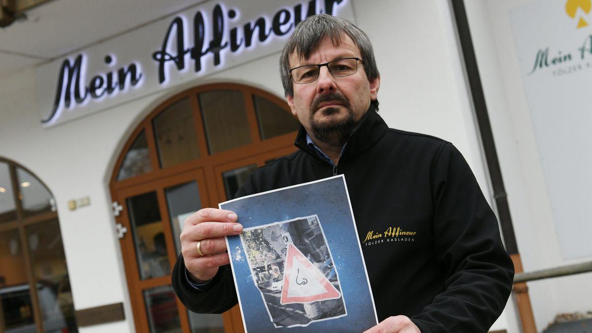 Der Geschäftsführer des Tölzer Kasladen, Wolfgang Hofmann steht mit einem Foto der Protestschilder vor seinem Laden.