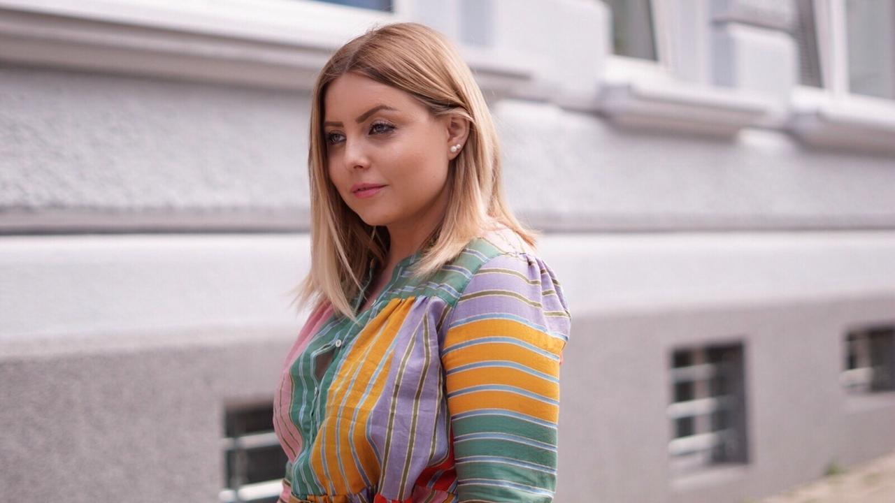 Bloggerin Deborah Fikentscher in einer bunten Bluse.
