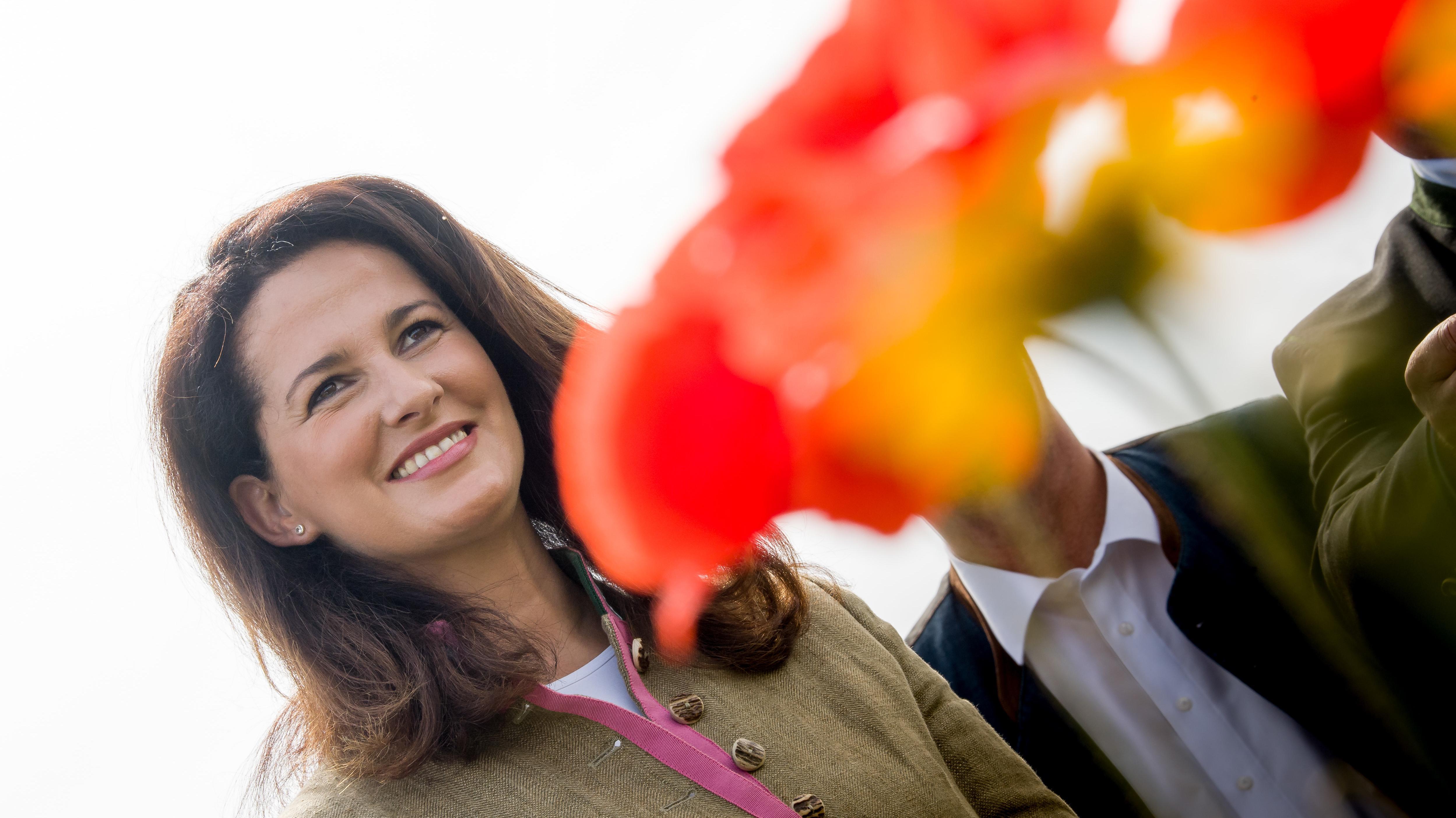 Michaela Kaniber (CSU), Staatsministerin für Ernährung, Landwirtschaft und Forsten steht hinter einer Mohnblüte.