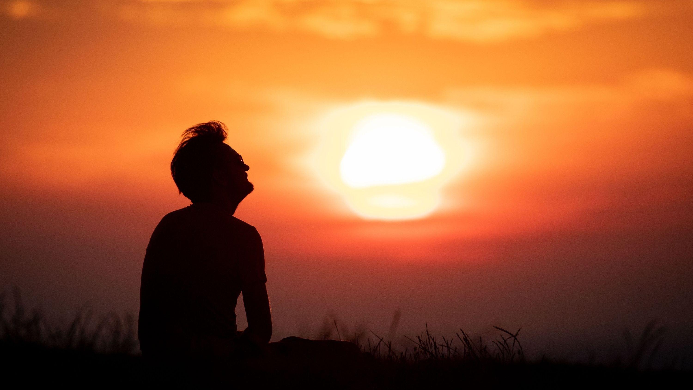 Mann sitzt vorm Sonnenuntergang