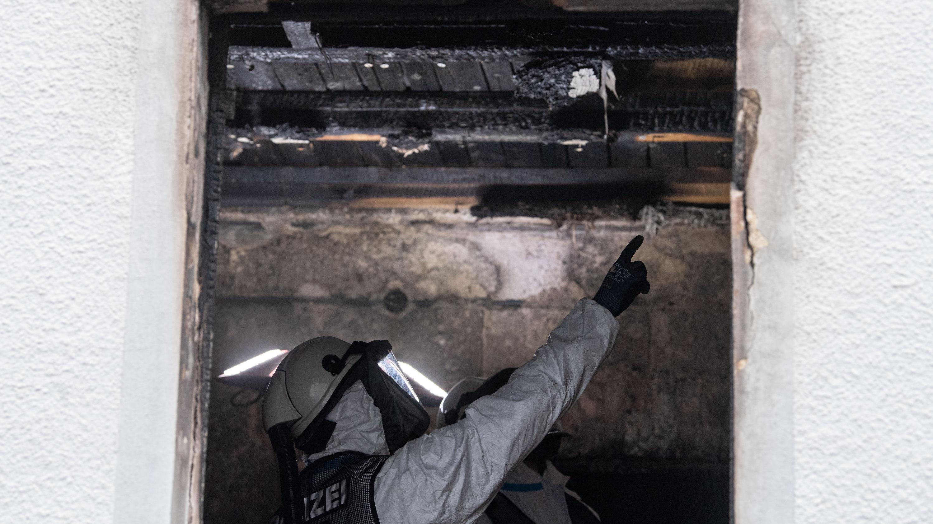 Ein Kriminaltechniker der Polizei in Atemschutzkleidung begutachtet im ausgebrannten Haus die Schäden.