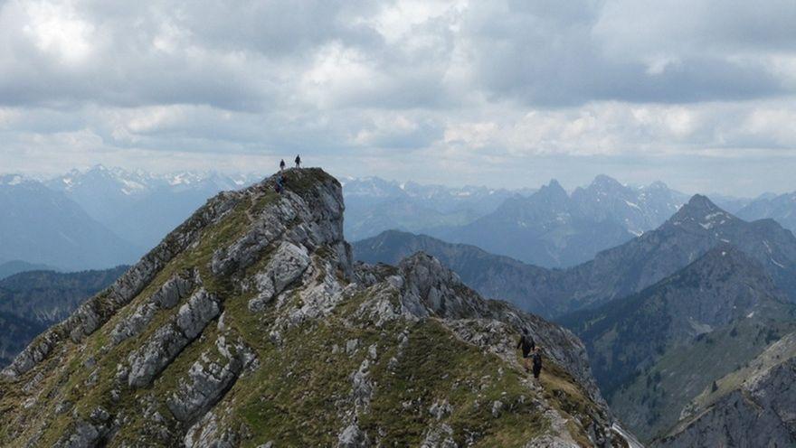 zwei Bergsteiger auf felsigen und ausgesetzten Westgrad der Hochplatte, dahinter Bergpanorama