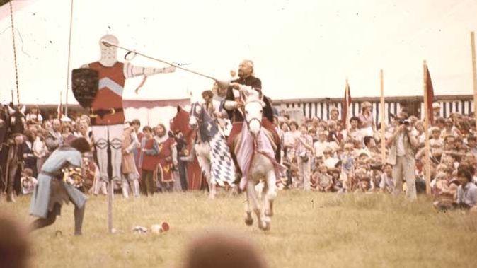 Auf einer Wiese versucht ein Ritter zu Pferd mit der Lanze einen Ring zu angeln