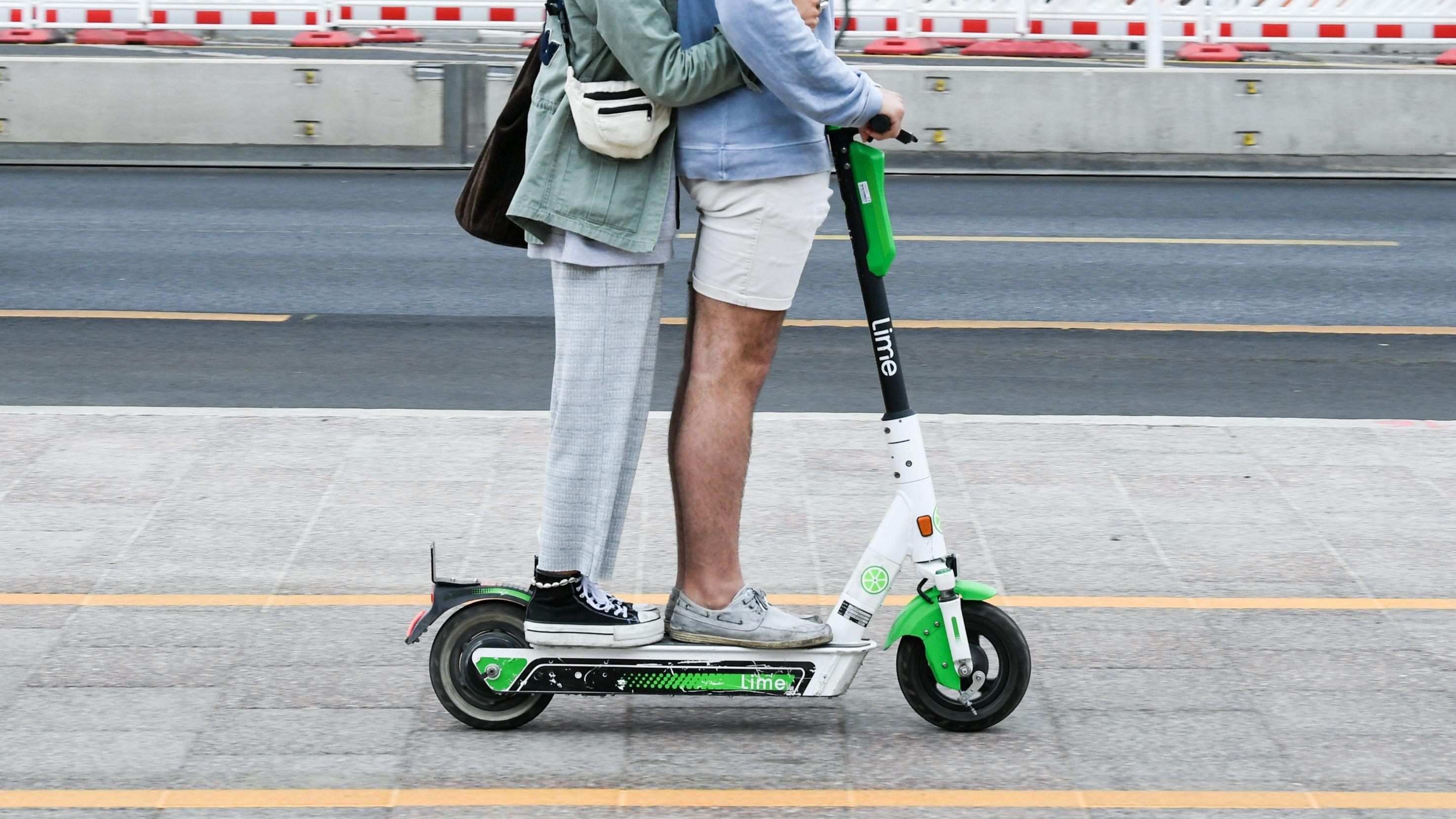Zwei Personen fahren gemeinsam gleichzeitig auf einem E-Tretroller. Das ist jedoch verboten.