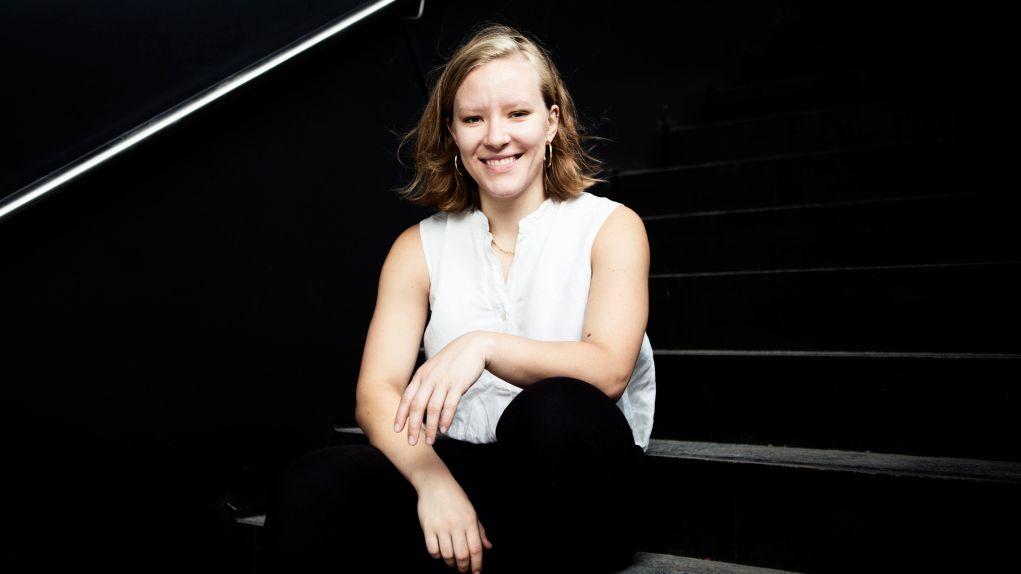 Raphaela Edelbauer, sitzend in weißer, ärmelloser Bluse auf einer schwarzen Treppe, lächelt