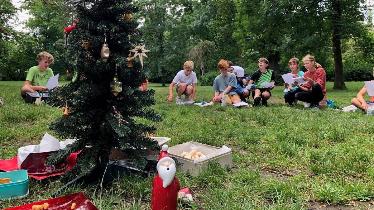 Ein geschmückter Weihnachtsbaum, dahinter Kinder, die Weihnachtslieder singen.